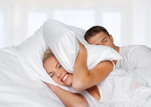 Snoring. Couple in bed while the woman is trying to sleep